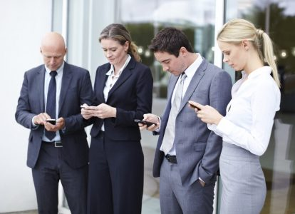 Group of four male and female executives using their cellphones outside their office