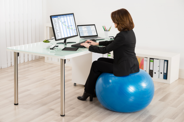 woman seated a ball chair in her office