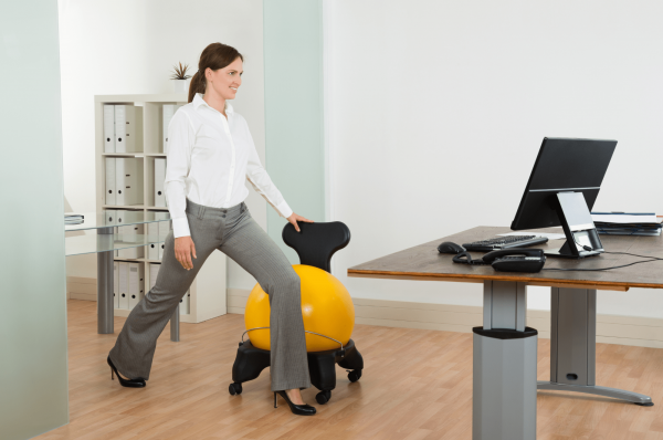 woman stretching beside ball chair in her office