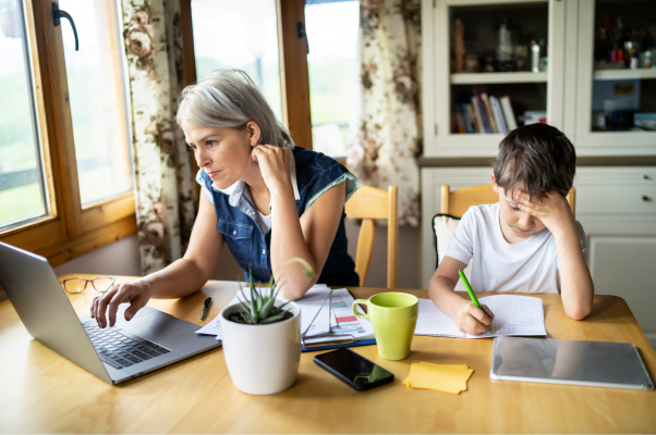 Woman working at home with her son